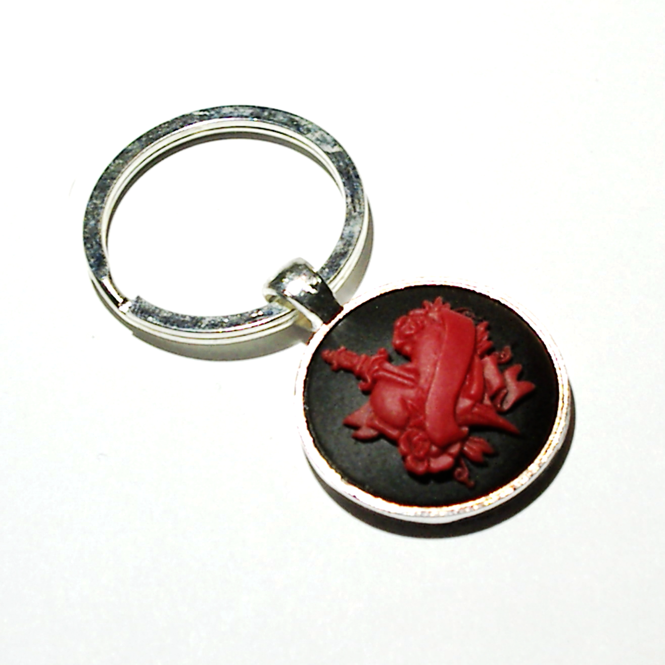 25mm red on black cameo of a heart pierced with a dagger, set in a silver plated bezel frame, with a matching silver split key ring.