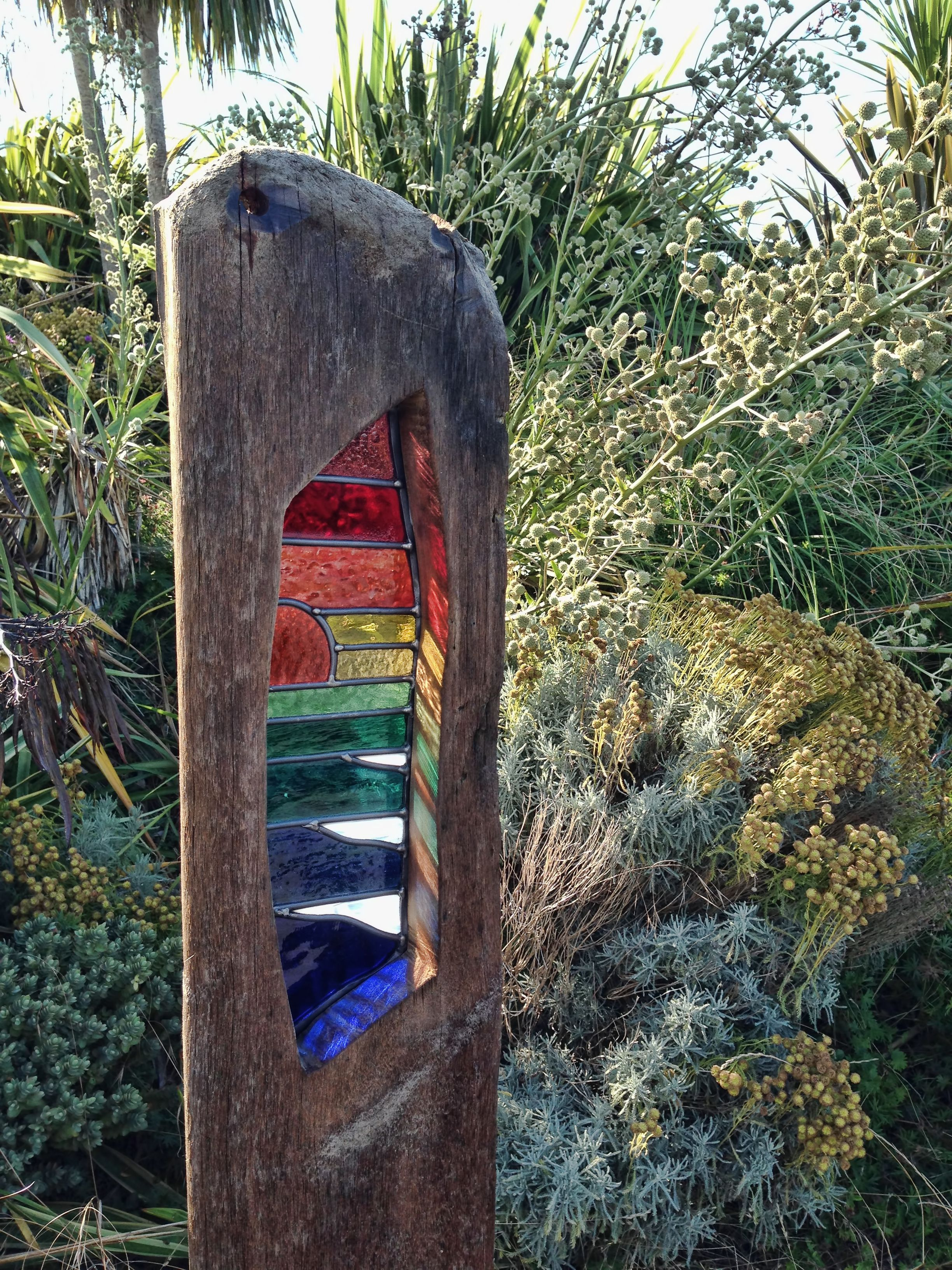 Quinton Gauntlett stained glass sculpture. reclaimed seawood groyne with waves at sunset stained glass art.