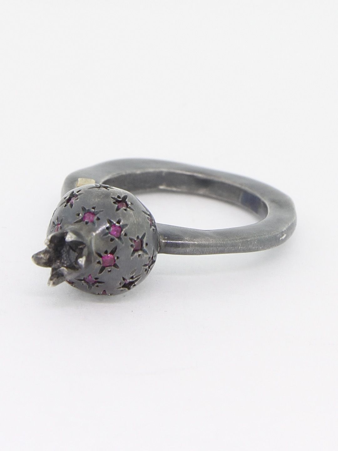 From Rosa Maria, this oxidized silver cocktail ring features a pomegranate fruit embellished with rose-cut rubies set into cross-hatched stars, the irregular shape of the band is a classic characteristic in Rosa Maria jewelry