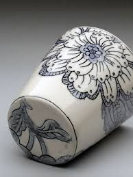 molly hatch - she draws into leather hard clay with a caligraphy pen, cleans well with dry brush, paints slip over pot, when dry cleans off all slip with a sponge (leave it in drawn marks). Bisque fires piece then paints in under glaze colour, glazes piece with clear glaze then fires cone 6.