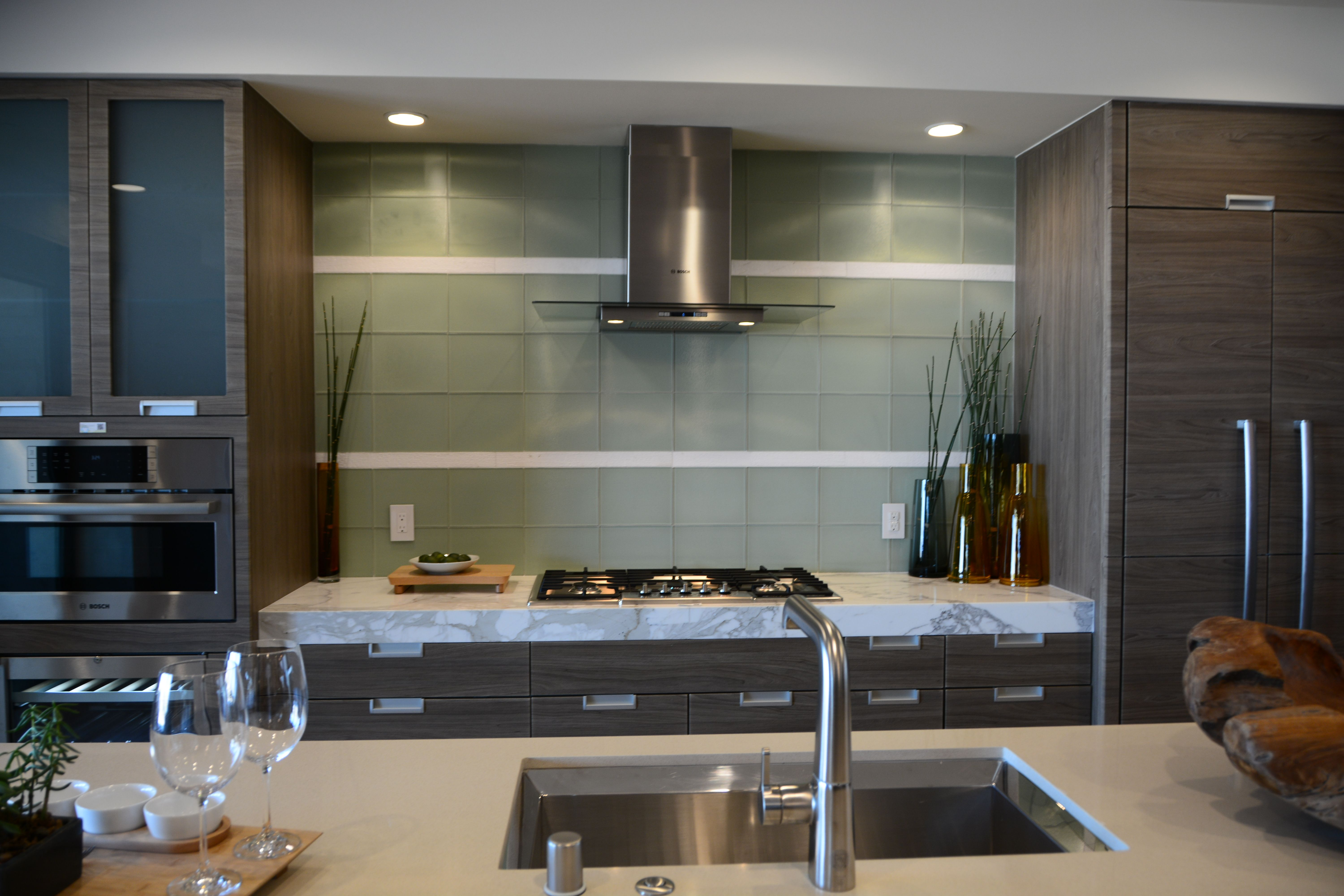 kitchen design with no top cabinets. fridge and freezer on one side ovens other open space in center for  coffee bar