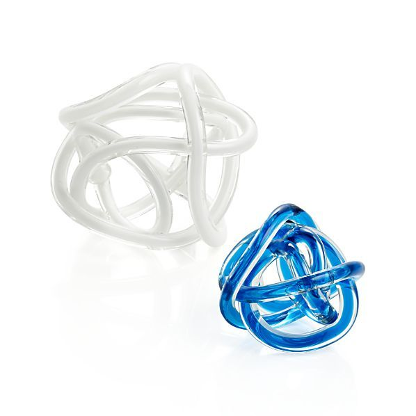 Skilled glassmakers use a special tool to pull molten glass and carefully form it into a mesmerizing knot. Available in white and blue, these charming decorations make a lovely centerpiece or table accent.