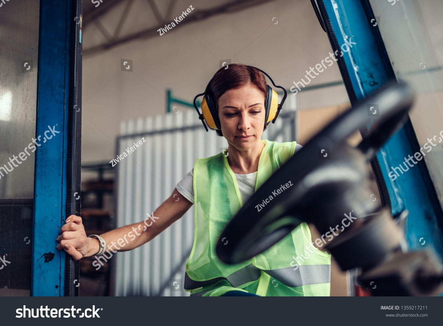 Woman forklift operator at industrial factory entering