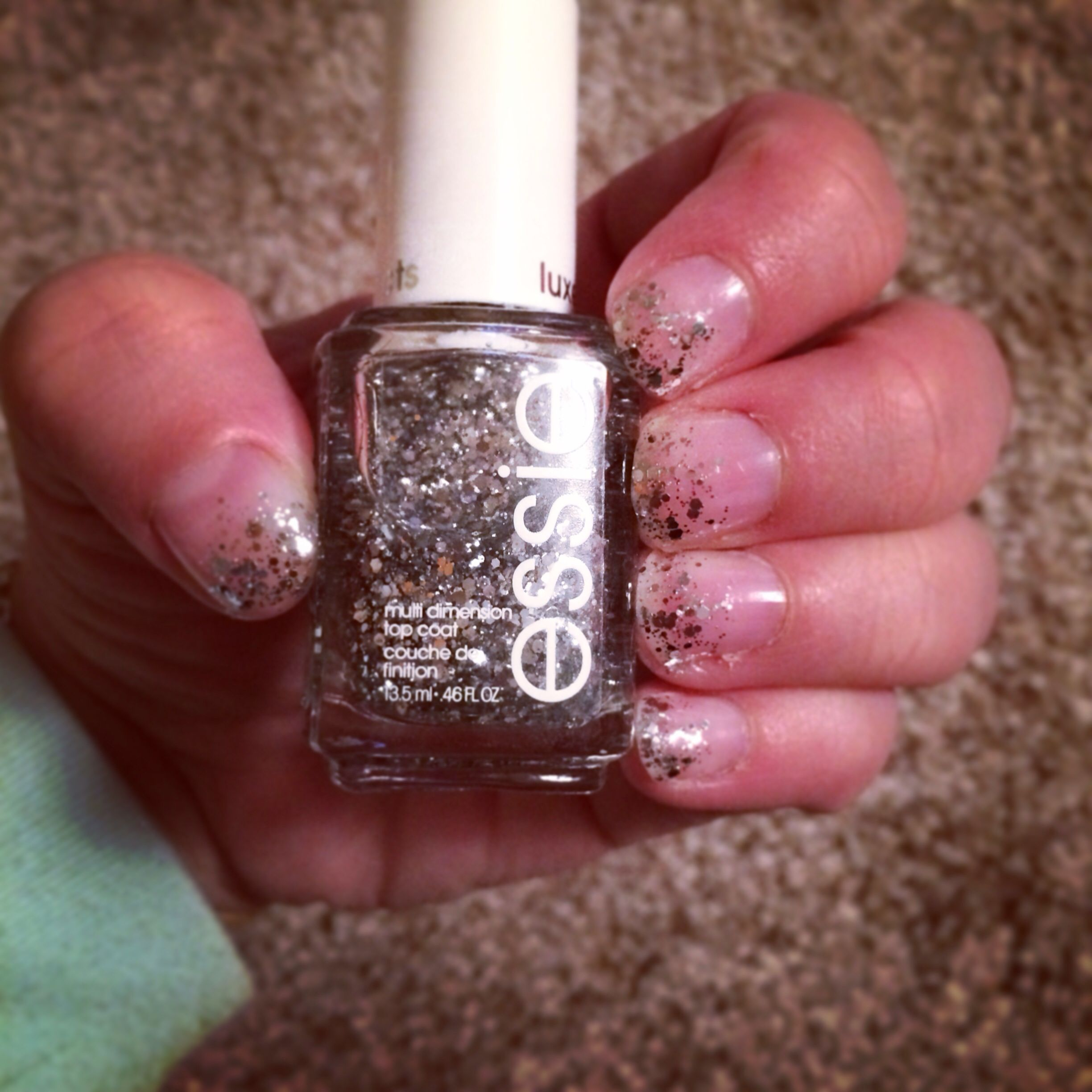 Sparkly French tips. Light pink polish with silver ombré sparkles on the tips.