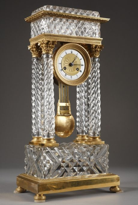 An important cut-crystal and ormolu mantel clock with four twisted columns imitating a classic temple, Corinthian capitals and gilt bronze bases adorned with twisted patterns. They support the dial...