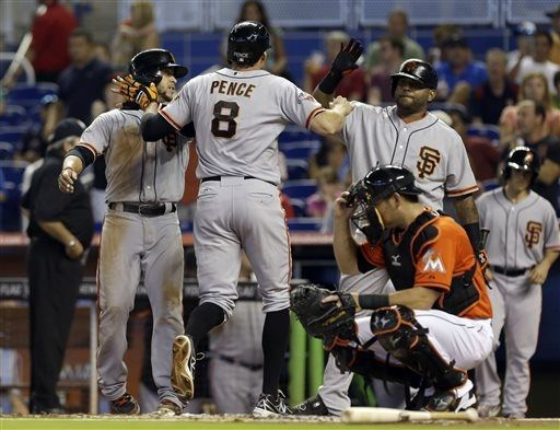 San Francisco Giants' Hunter Pence (8) is greeted by teammates Gregor Blanco, left, and Pablo Sandoval, right, at home plate after hitting a two-run home run against the Miami Marlins in the first inning of a baseball game on Sunday, Aug. 18, 2013, in Miami. Blanco scored on the home run. (AP Photo/Alan Diaz)