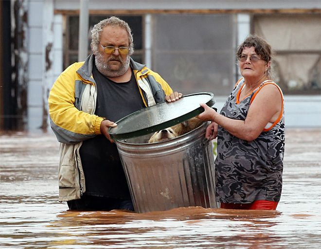 George and Susan Kruger make one of three trips with their animals from their flooded house to safety on Sunday, May 24, 2015 in Purcell, Okla. Rising water from overnight rains began to rise early in the morning. The Krugers refused to leave their home and made several trips to retrieve five dogs and a baby chick. (Steve Sisney/The Oklahoman via AP)