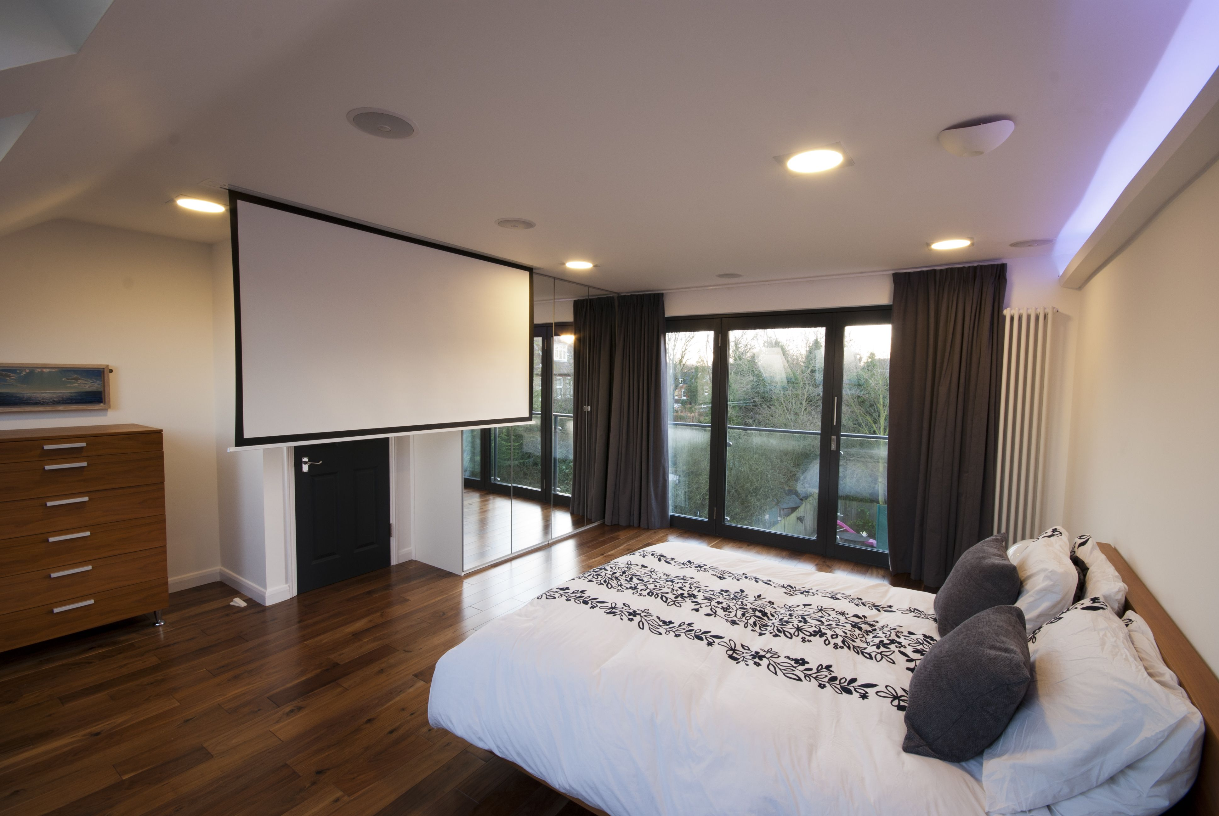 Loft Conversions Bedroom With French Doors And A Cinema Screen Built Into  The Ceiling