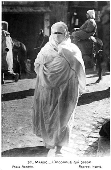 From old postcards. Morocco: the unknown woman goes by (woman wearing a haik which was worn mostly in cities until the 1950s when it was replaced by djellabas, litame and hood.) From Les femmes du Maroc d'antan ou l'incarnation de la puissance féminine