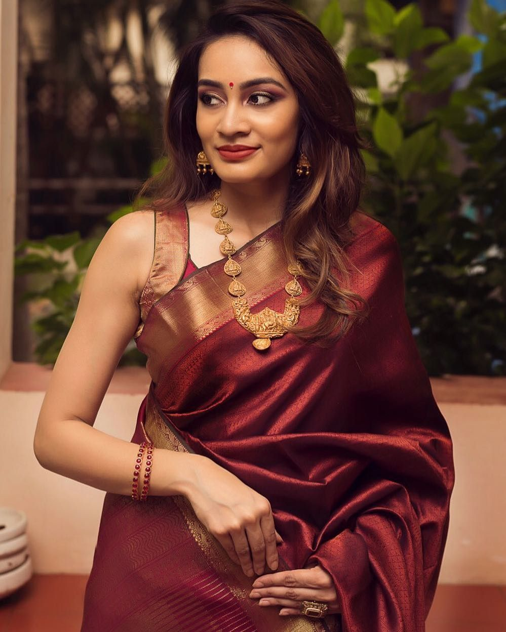 In a gorgeous maroon color saree and sleeveless blouse design in 2020   Sleeveless blouse ...