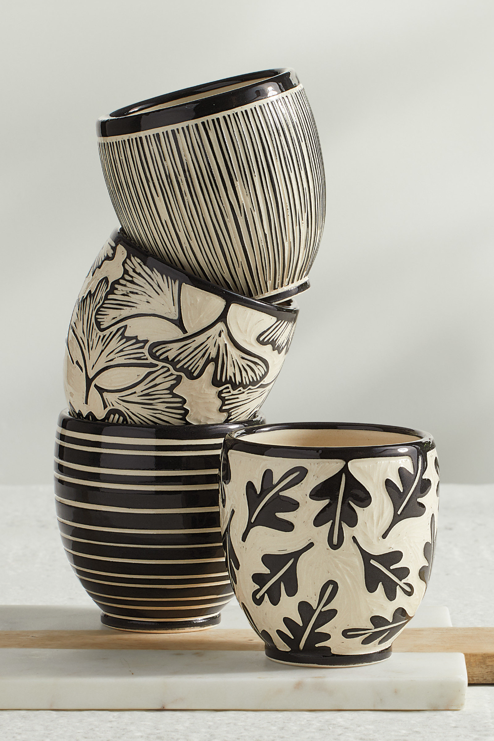 Ceramic Cups by Jennifer Falter. A whimsical wheel thrown ceramic cup, decorated with sgraffito using black slip, featuring a a pattern of oak leaves. Glazed to give a glossy finish inside and out. Each piece is unique and will vary slightly from piece to piece. Holds approximately 16 oz. of hot or cold liquid. Microwave and dishwasher safe. Signed by the artist with a stamp.