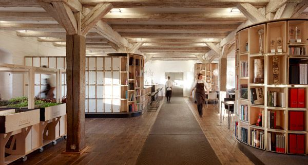 The new Noma food lab is now part of the same building that Noma is in – an eighteenth-century warehouse. From this wide shot we see they have microgreens growing on the left, bookshelves on the right. Behind the shelves we see tables (for dining?) and the cooking area in the back left.