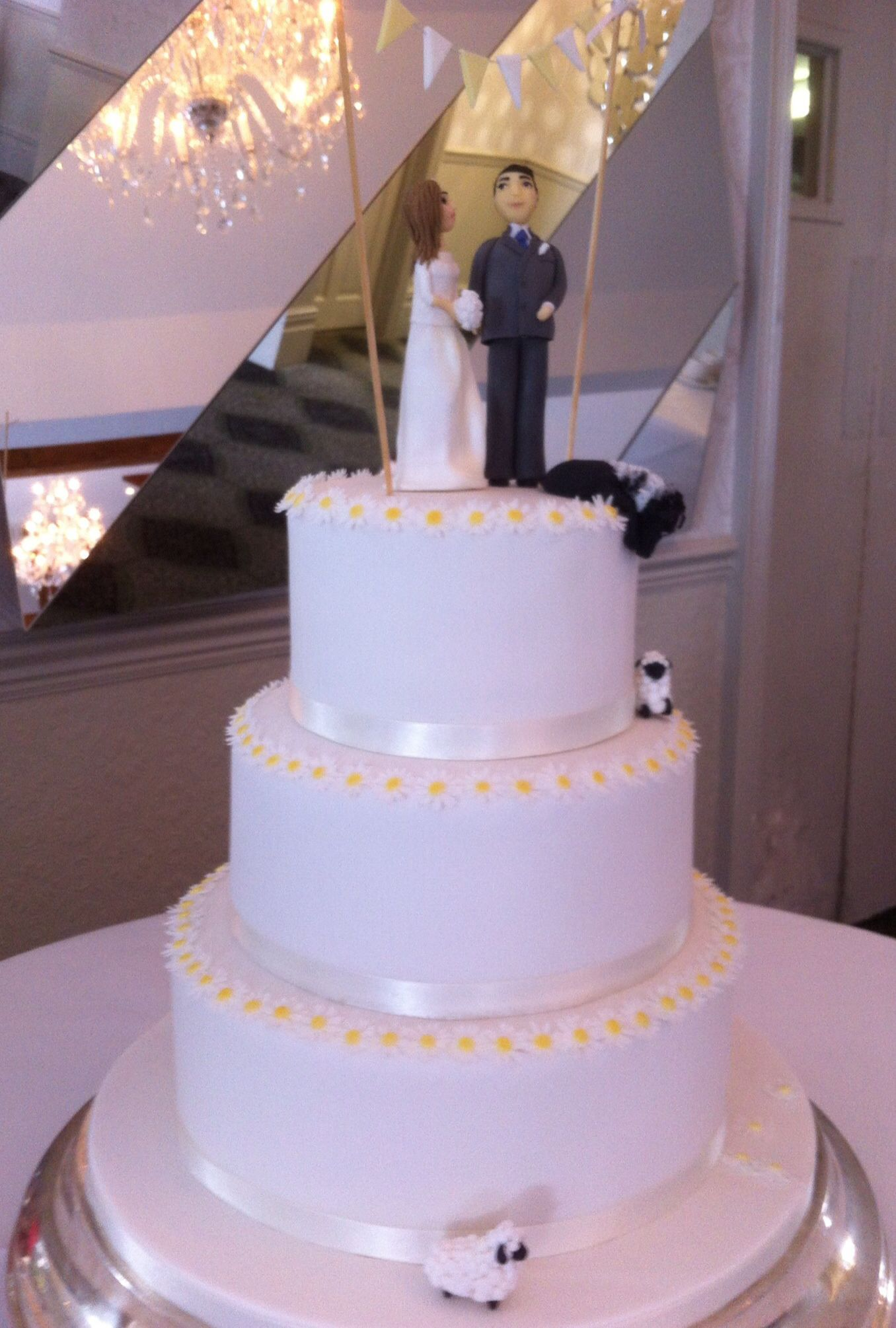 Delicate daisy wedding cake with sugar bride and groom topper sheep
