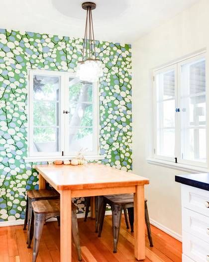 Lively patterned wallpaper brighten up a cozy dining space