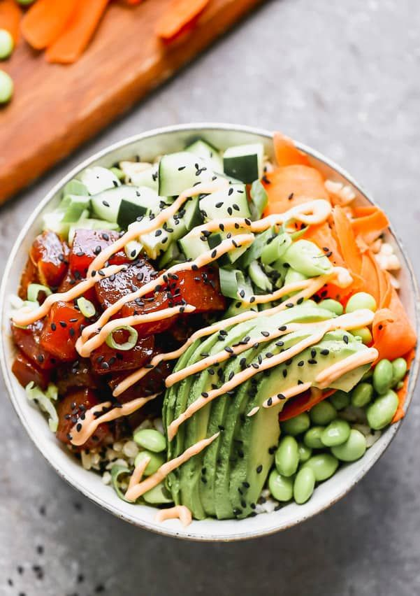 Poke bowl with ahi tuna, cucumbers, avocado and carrots all in a bowl.