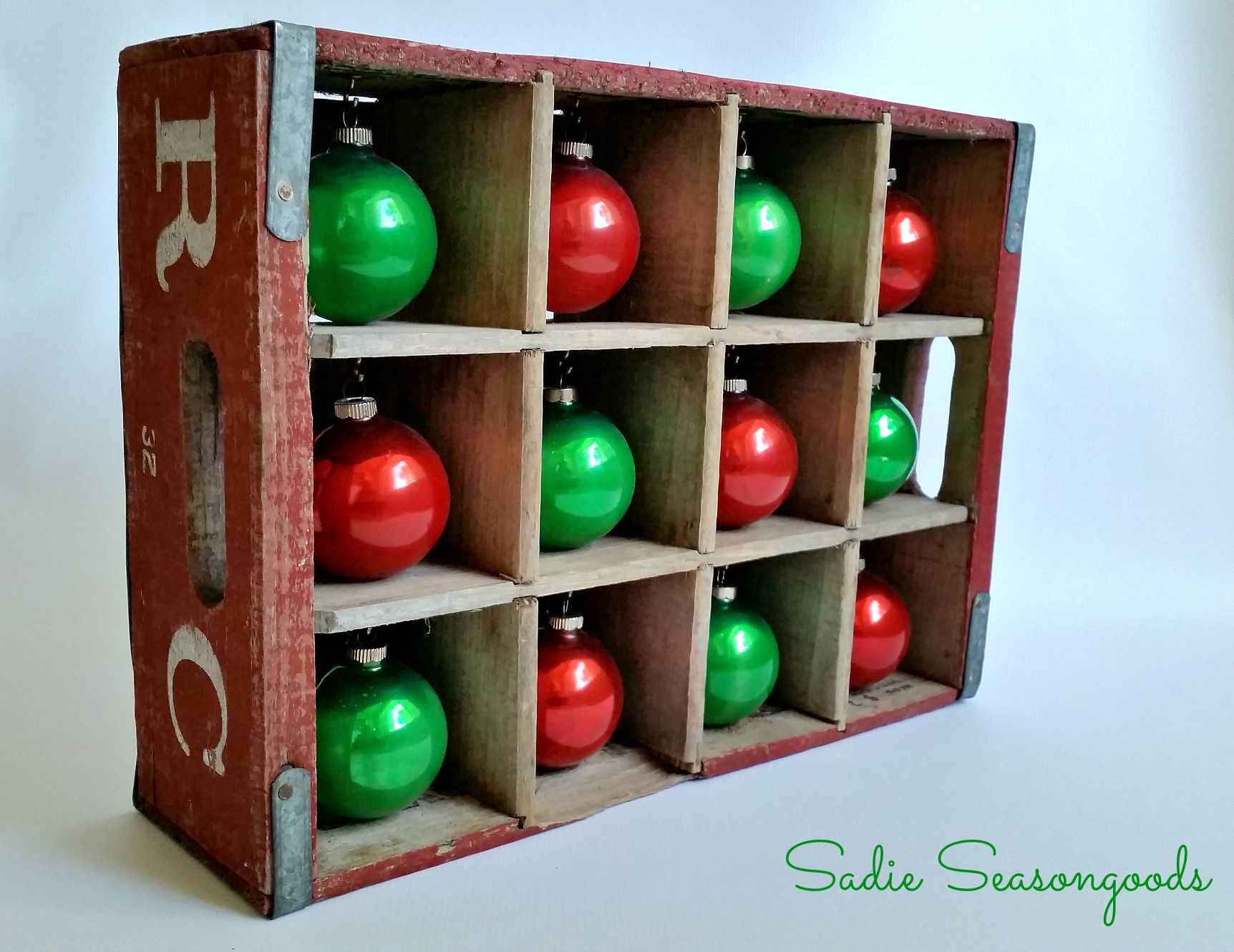 love using this antique 1970's RC Cola Crate to display my vintage Shiny Brite ornaments! Perfect for a tabletop or my mantel. The secret is that the holes in the crate are larger, perfect for standard-sized Christmas ornaments! #sadieseasongoods