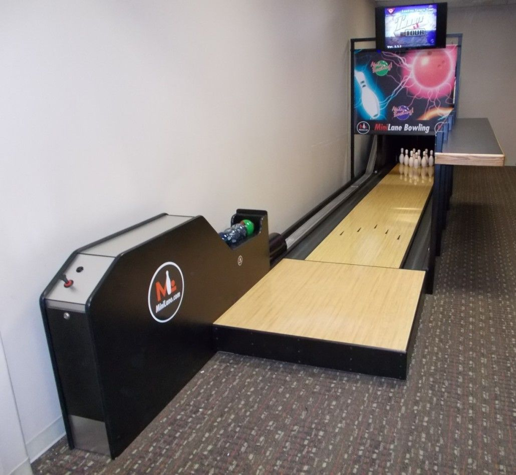 a mini bowling alley in a basement of a regular home. | the