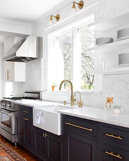 Classic kitchen with black shaker cabinets and modern brass hardware, apron sink, carrara marble backsplash and open shelving.