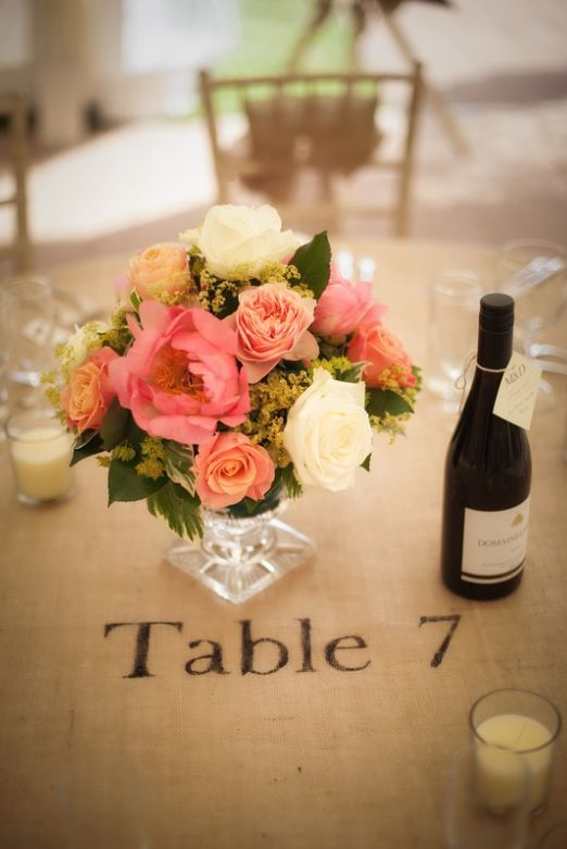 Coral wedding flowers with hessian tablecloth and wine bottle labels for a summer wedding