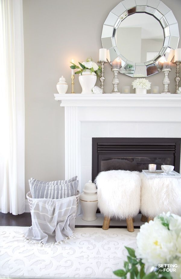 How To Decorate Your Living Room For Summer with flowers and greenery. #summer #livingroom #fireplace #mantle #flowers #greenery #hearth #decorating #mirror #gingerjars
