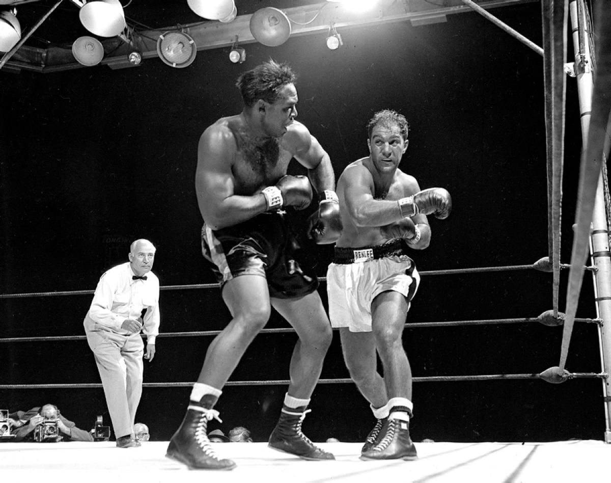 b92e0a38b53a Rocky Marciano (r.) misses with a right as Archie Moore turns away during  their 1955 Yankee Stadium match.