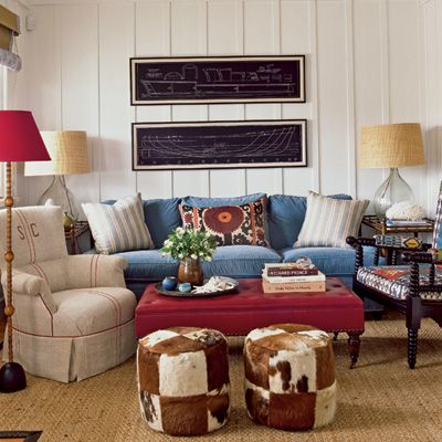 This room is awash in interesting texture: cowhide stools, a vintage grain sack-covered chair, a velvet sofa, raffia lamp shades, a leather ottoman, and a jute rug.