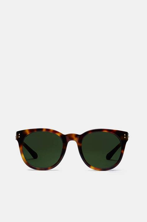 Face-flattering tortoiseshell tones meet green lenses in these elegantly rounded sunglasses from Linda Farrow. Suitable for both men and women, they have a straight top lens frame that curves to meet a bulging, high-sitting nose bridge. Signature details include 22-karat gold plated titanium studs on the ridge top corners as well as the smoothly angular temples. In addition to a soft leather pouch and a hard black case, these glasses are accompanied by a snakeskin-textured jewelry box.