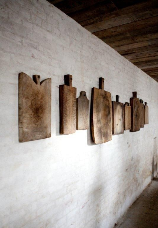 The rustic feel of old cutting boards hung along a wall.