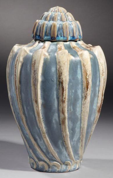 """Manufacture Nationale de Sèvres Coquillage, 1902    Vase en grès porcelainique et son couvercle d'origine, de forme ovoïde à encolure concave, col plat et base circulaire. Couvercle étagé. Décor de côtes en relief légèrement obliques et espacées. Couverte émaillée à cristallisations bleu-gris et bleu-roi. Côtes de couleur beige ponctuée de brillances brunes. Signé du cachet Sèvres et S1902 dans un triangle. Marqué """"modelé"""" sous la base sous couverte. Ht: 27 cm, D: 17 cm"""