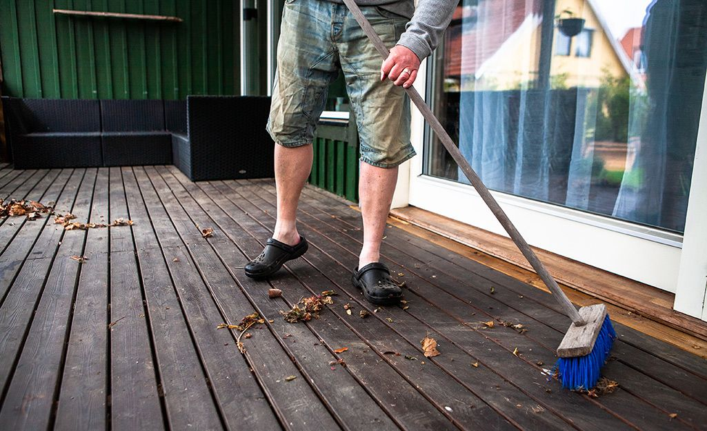 A person sweeps a deck with a push broom. in 2020 Clean