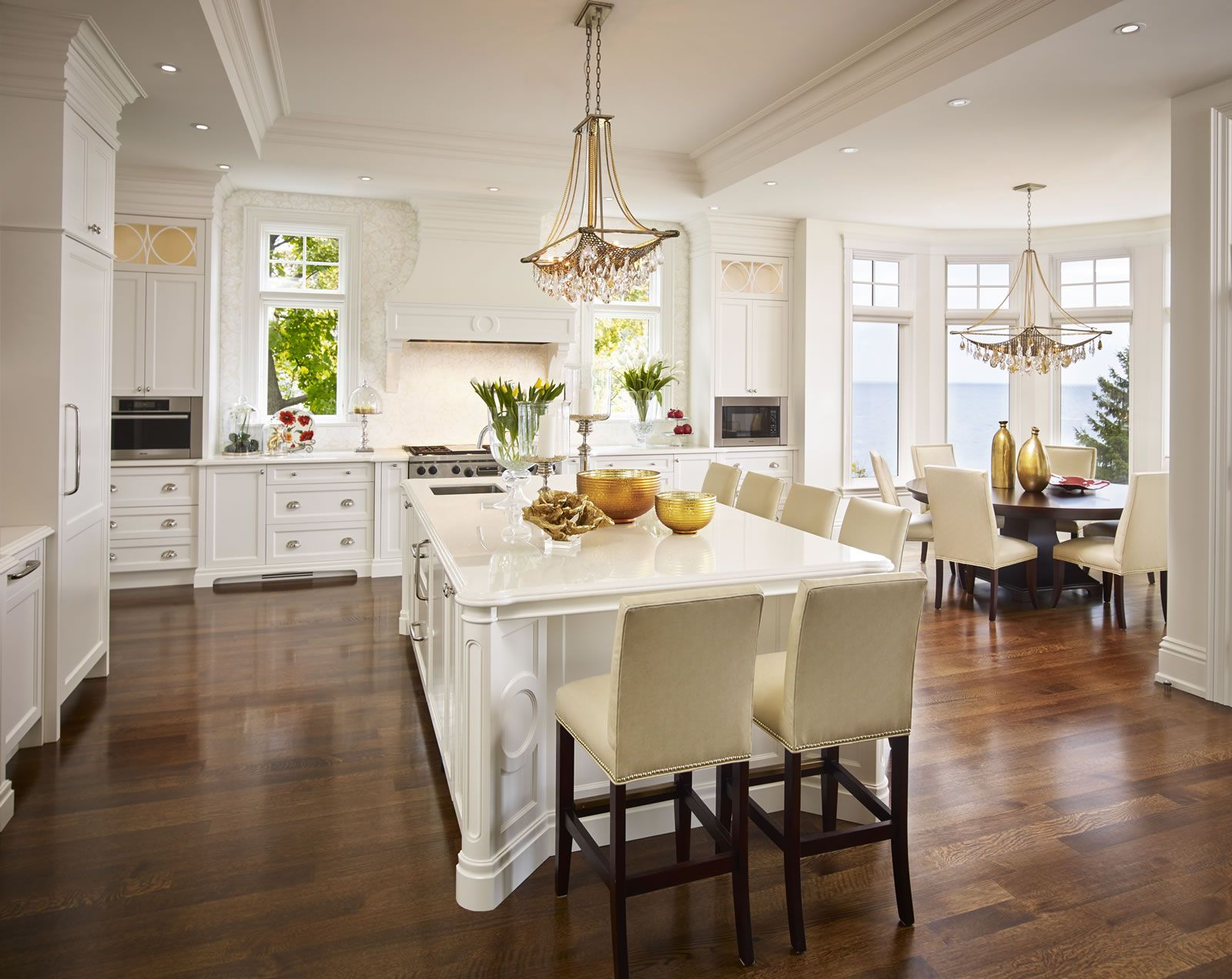 A sun-filled classic kitchen with bespoke lighting and panoramic lake views. Designed by Regina Sturrock Design Inc.
