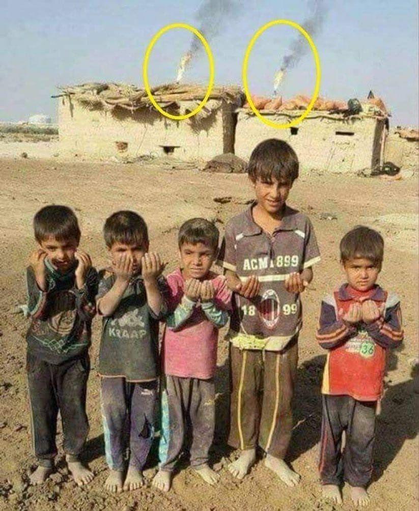 أطفال عراقيون في ضواحي مدينة البصرة حفاة وبثياب رثة يدعون الله أن يرزقهم ما يفطرون به وتظهر خلفهم مباشرة مشاعل حقل الرميلة النفطي ال Baghdad Fair Grounds Art