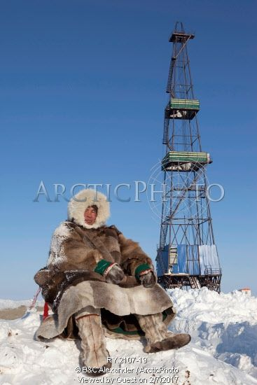 Image of jakov vanuito, a nenets reindeer herder, sits infront of a gas drilling derrick near tambey in the south tambey gas field. yamal peninsula, western siberia, russia by ArcticPhoto