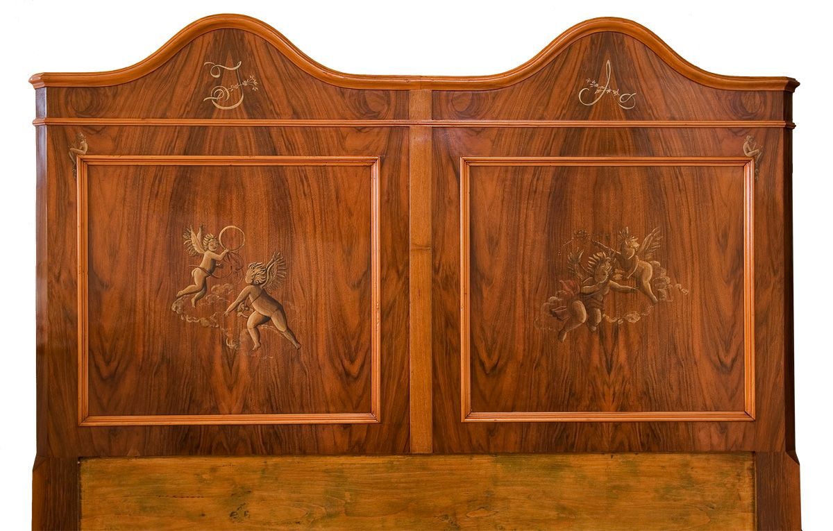 an italian walnut headboard from late '800 decorated with little angels, classical figures and owner's monogram; by ORNAMENTS, Rome