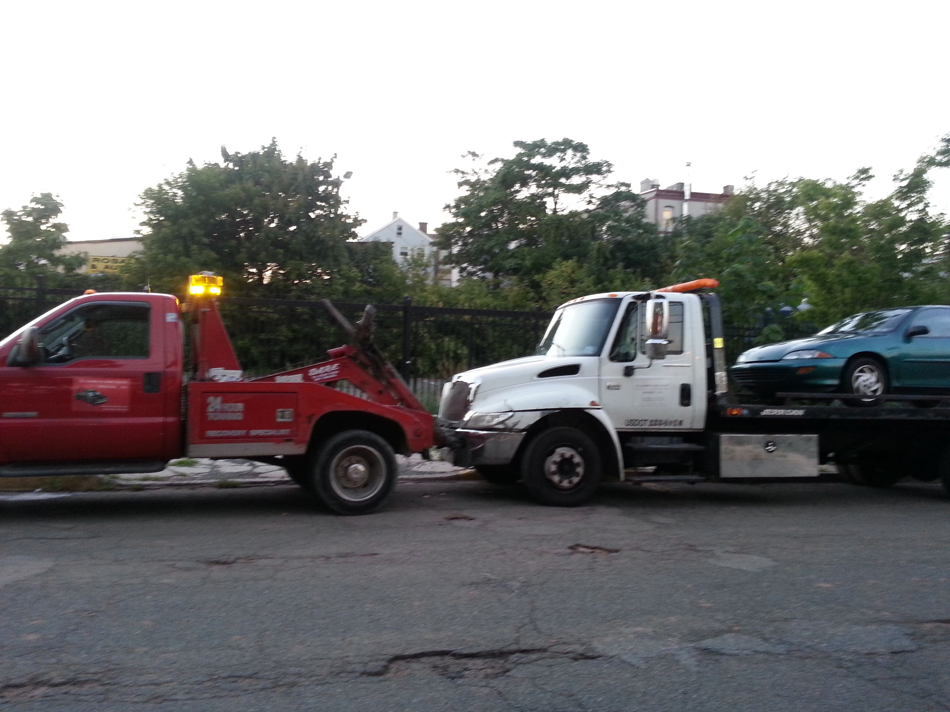 Pin of out tow trucks towing a junk car away. Trucks