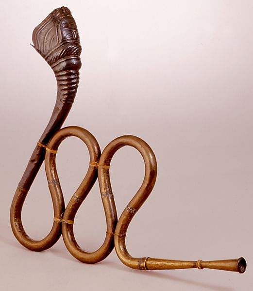 """NAGFANI  Brass tubing with flared copper bell, stylized serpent head. Used by holy men (sadhus) of India during ritual ceremonies and also by story tellers and street performers. Its name literally means """"snake or cobra hood.""""  Gujarat or Rajasthan, India, 20th century"""