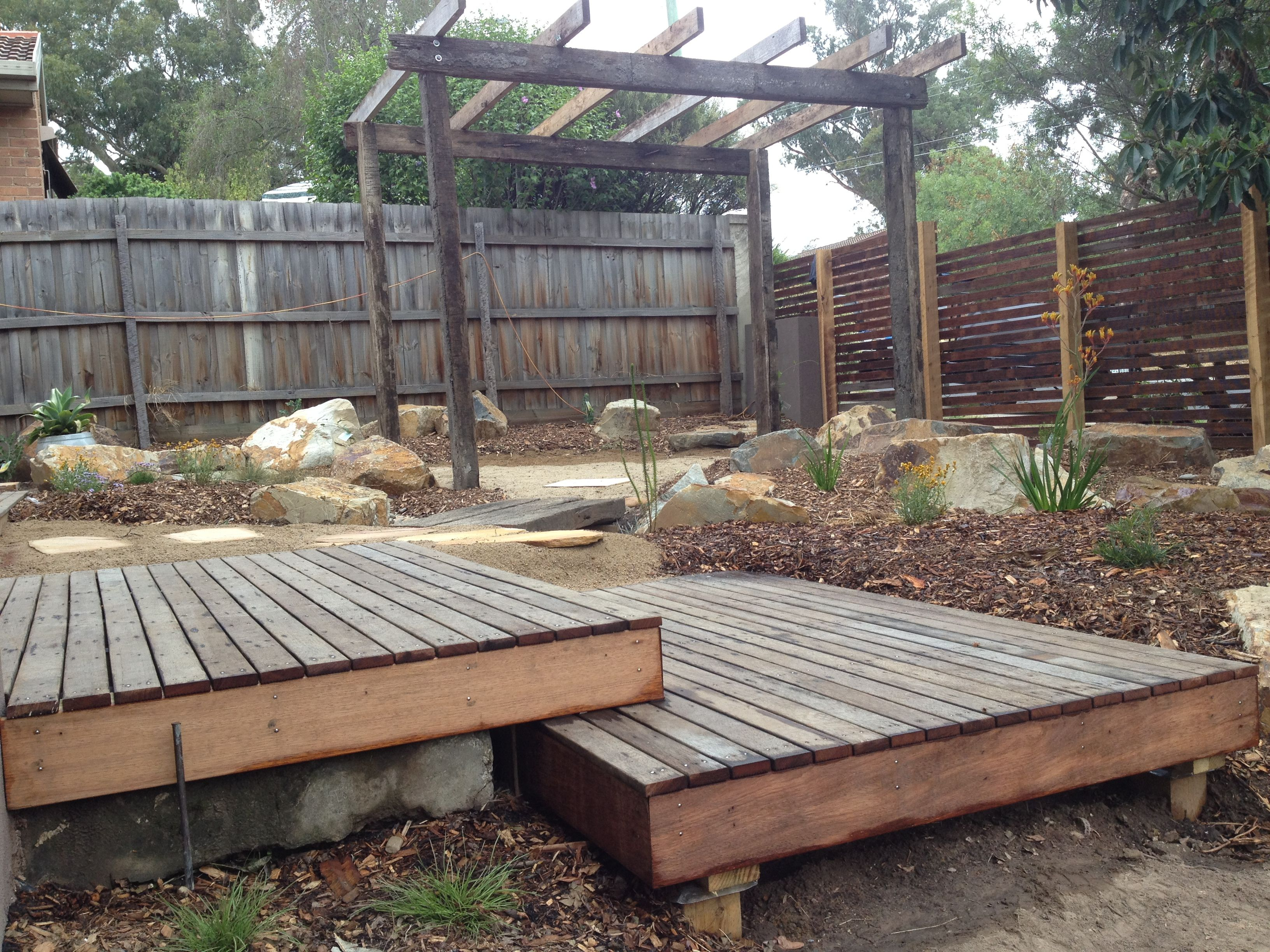 Native shrubs and grasses around a dry riverbed with for Garden decking near me