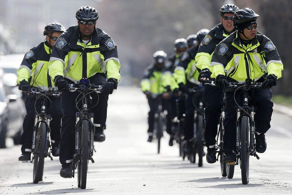 Boston police on bicycles patrol on Commonwealth Avenue following the explosions at the finish line of the Boston Marathon.