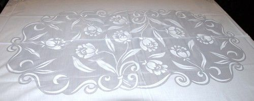 Organdy cotton tablecloth with flowers and leaves in center and border.