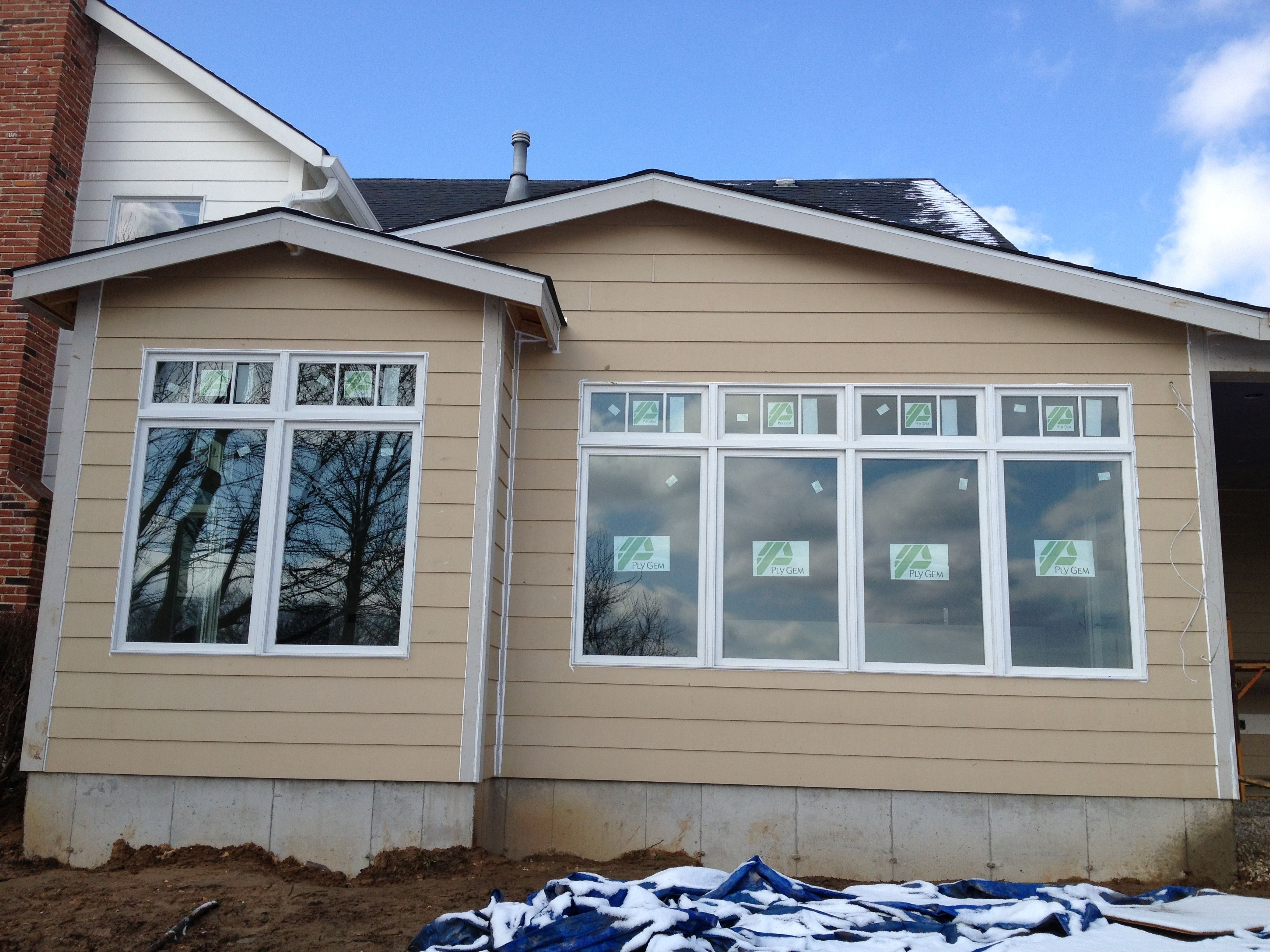 Ply Gem Mira wood clad quad and twin mulled windows with quad and twin transoms that have simulated divided lite grilles (SDLs).  Exterior color is White.