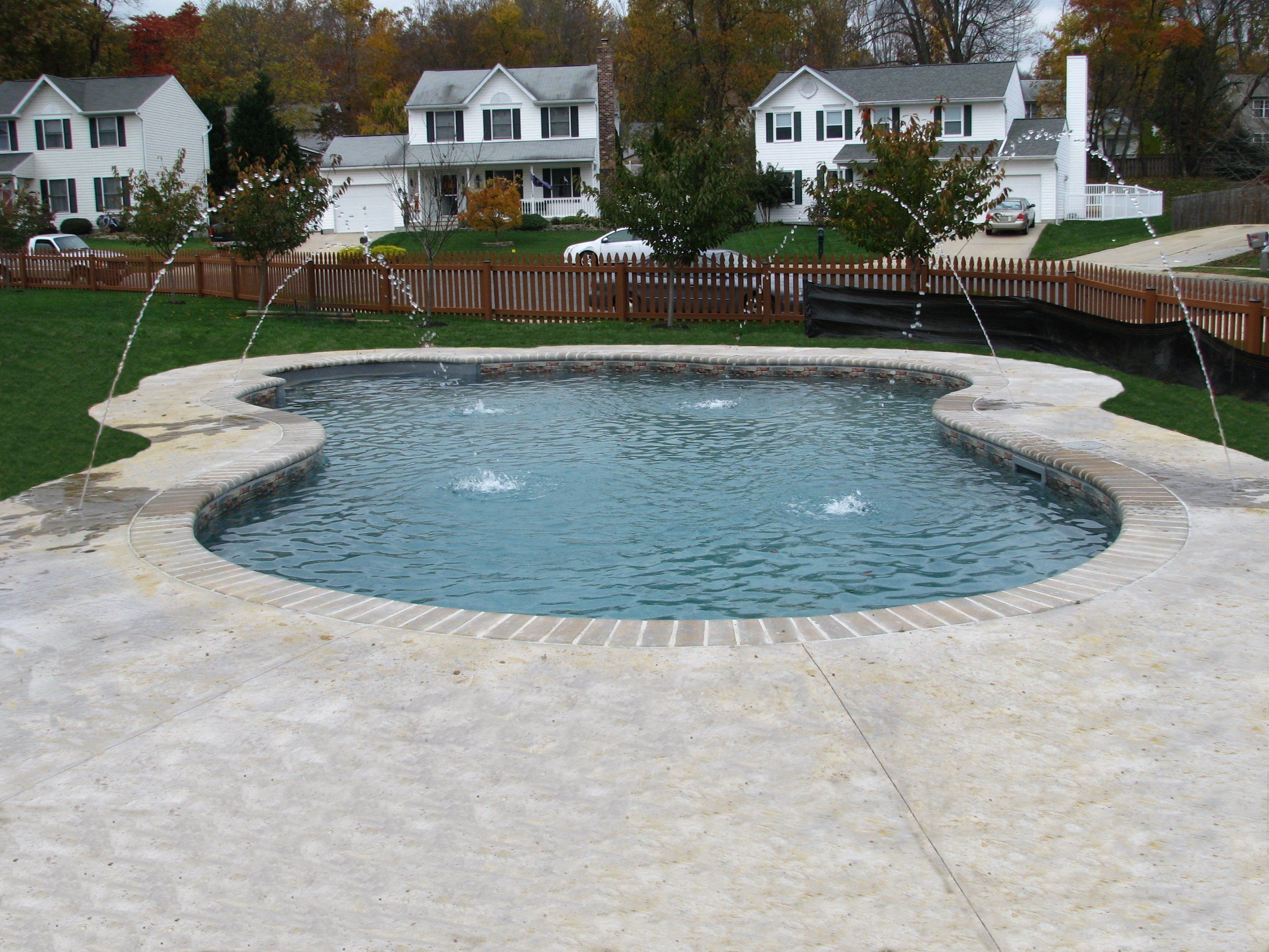 Freeform vinyl with brick coping stamped concrete and deck jets our beautiful swimming pools for Paint for inground swimming pool coping