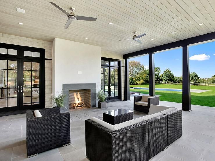 Chic covered patio features a plank ceiling dotted with modern