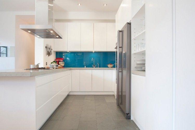 weiße Einbauküche mit blauem Glas Spritzschutz