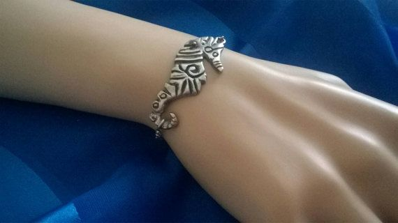 A beautiful sterling silver seahorse. All hand carved. The seahorse is curved to follow the contour of your wrist and has been slightly oxidised to show detail. Thick solid silver. The seahorse is just under 1 and 3/4 inches long. The bracelet chain will be customised to fit your wrist size.
