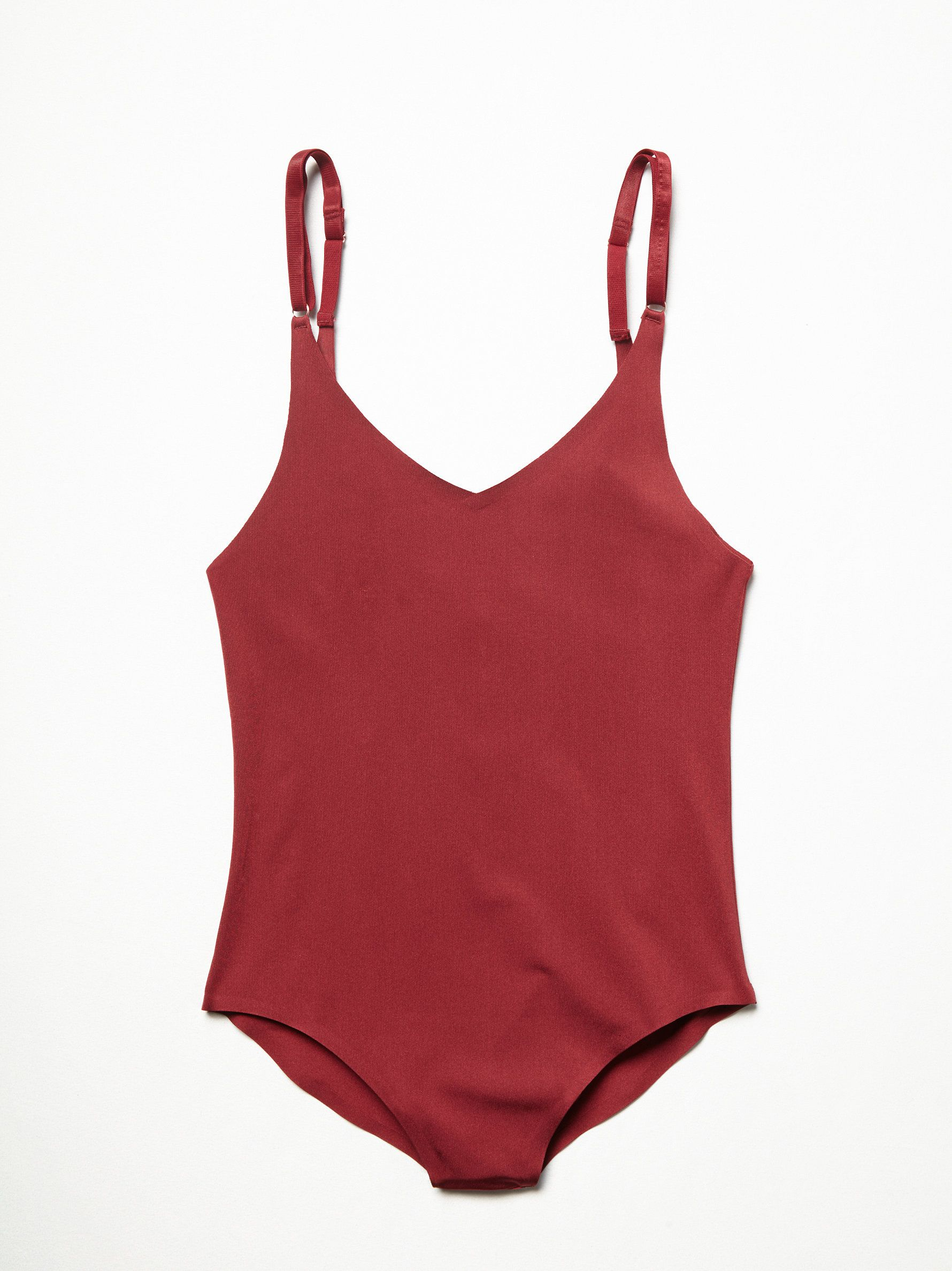 City Slick Bodysuit   In a silky fabric this seamless fabric this easy bodysuit features a V-neckline in front and back and adjustable straps. The perfect layering piece. Snap closures on the gusset.