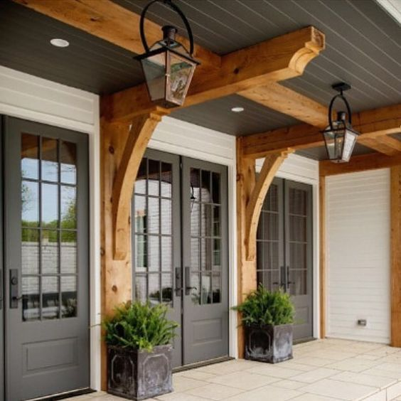 Farmhouse front porch with gray doors and wooden beams for French doors front of house