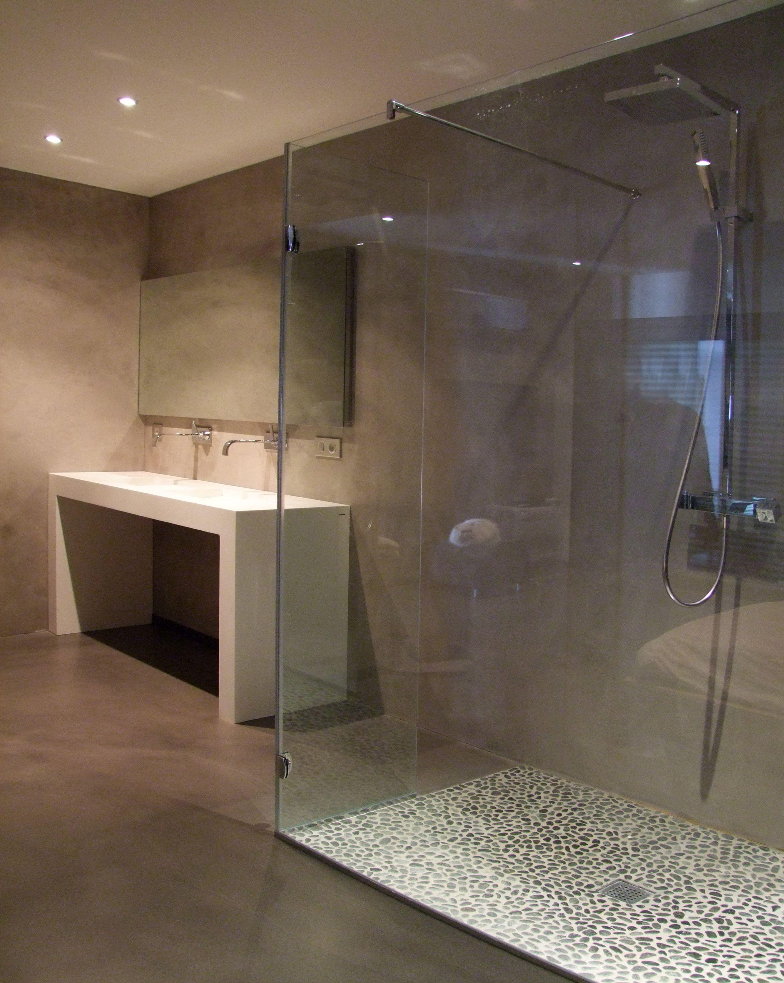 Dans une salle de douche, sol en béton ciré gris taupe et enduits