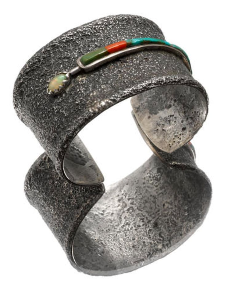 Cuff | Charles Loloma. Tufa cast; surmounted by a narrow tapered channel containing turquoise and coral, an opal bezel set at one end.