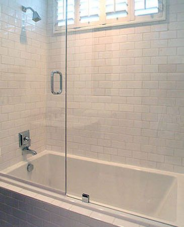 Clean Crisp White Bathroom With White Beveled Subway Tiles Shower Surround Glass Sliding Shower Doors And Pol Tub With Glass Door Glass Tub Bathrooms Remodel