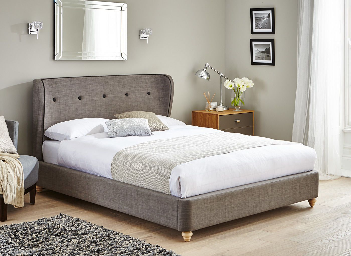 Upholstered in a grey woven fabric, this sleek bed is a